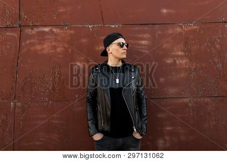 Young American Hipster Man In A Black Baseball Cap In Sunglasses In A Leather Black Jacket In A Fash
