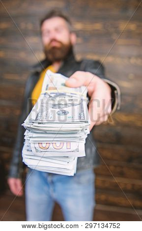 Man give cash money bribe. Richness and wellbeing. Mafia business. Man brutal bearded hipster wear leather jacket and hold cash money. Illegal profit and black cash. Guy mafia dealer with cash profit poster