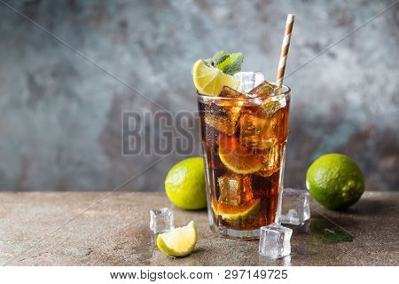 Fresh Made Cuba Libre With Brown Rum, Cola, Mint And Lemon On Gray Stone Background