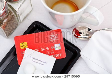 Photo of a credit card placed on a tray to pay for a restaurant bill. The card is a mock up designed and printed by myself, all the details including logos and hologram are generic.