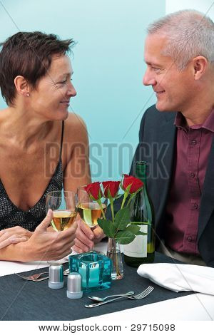 Photo of a mature married couple looking into each others eyes whilst sat at a table in a restaurant