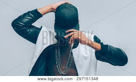 Afro American Urban Guy. Rapper Posing In Cap And Leather Jacket On Naked Torso. Head Tilted Down. R