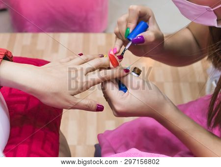 Close Up Of Female Hands Applying Transparent Nail Polish