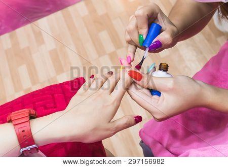 Female Hands Applying Transparent Nail Polish