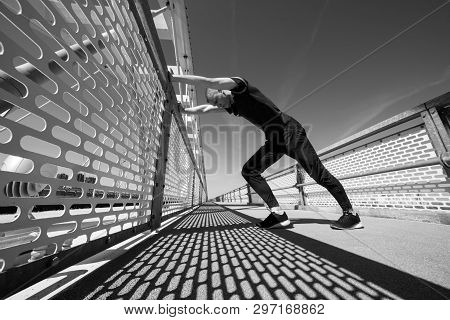 Attractive Young Male Athlete Stretching Before Running Outdoor.