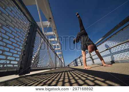 Strong Young Athlete Doing Handstand On The Bridge.