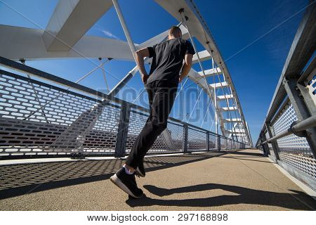 Attractive Young Male Athlete Running Outdoor  On The Sunny Day