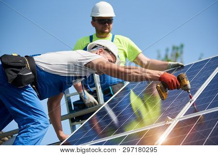 Two professional technicians installing solar photo voltaic panel to metal platform using screwdriver on bright blue sky copy space background. Stand-alone exterior solar panel system installation. poster
