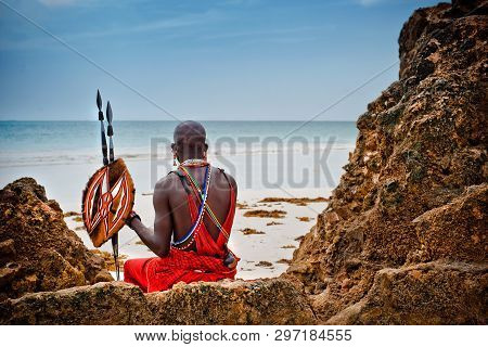 African Man Of The Maasai Tribe In Kenya Sits On The Ocean And Looks Into The Distance. The Flavor O