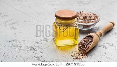 Linseed Oil, Bowl And Scoop Of Linseeds On Concrete Background, Copy Space. Omega 3 Source Concept