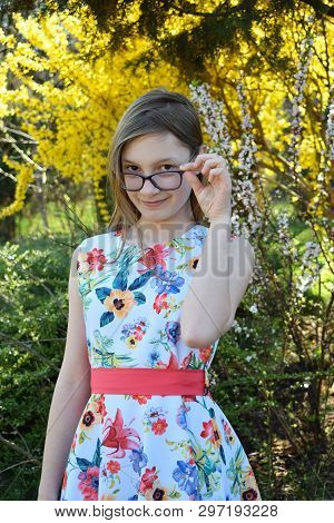Portrait Of Beautiful Girl With Brown Hair Looking Over Glasses And Surprised. Young Smiling Teneege