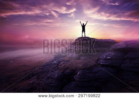 A Man Expressing Freedom By Reaching Up To The Sky As The Sun Sets In The Distance. Hopes And Dreams