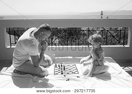 Father With Son On Balcony Play Chess. Child Play Chess With Father. Love And Trust As Family Values