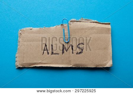 Submit alms, concept. Old torn cardboard on a blue background. poster