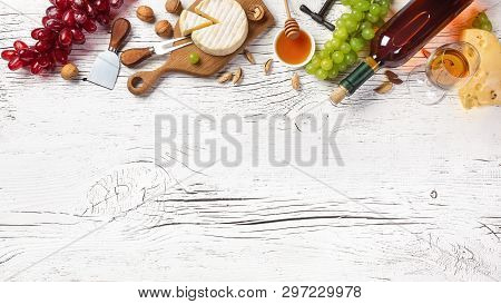 White Wine Bottle, Grape, Honey, Cheese And Wineglass On White Wooden Board. Top View With Copy Spac