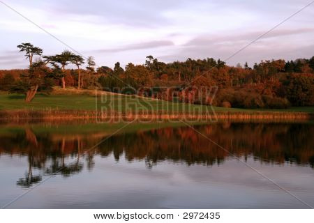 Tree Line Reflected Into Lake As The Sun Sets