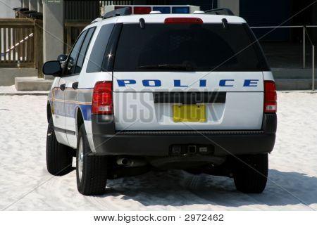 Back Of Beach Police Car Parked On Sandy Beach
