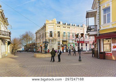 Feodosia, Crimea, Russia - March 08, 2019: People On A Small Square At The Intersection Of Pedestria