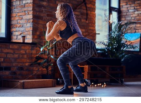 Pretty Young Women Is Doing Squat At Modern Loft. She Is Wearing Sport Leggings, Bra And Sneakers. W