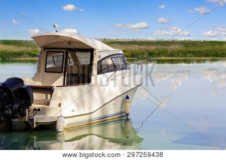 Big Luxury Fishing Boat With Cabin Moored Near River Or Lake Shore In Still Water. Blue Sky On The B
