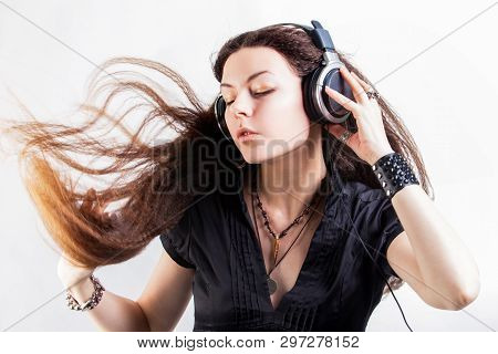 Young Stylish Woman In Large Headphones Listening To Music And Having Fun. Music Lover Girl With Fly