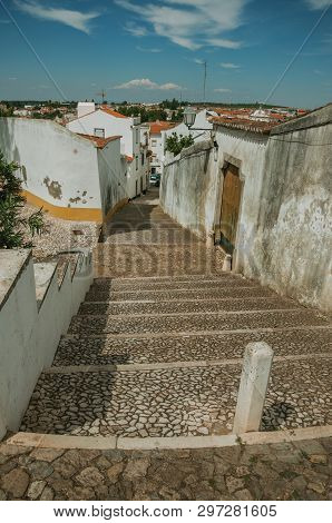 Narrow Alleyway With Steps On Slope With Old Houses And Stone Causeway, In Sunny Day At Estremoz. A