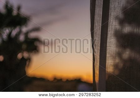 Countryside Landscape With Multicolored Sky At Sunset Dusk And A Curtain On The Foreground In A Farm