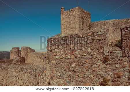Close-up Of Thick Stone Wall With Merlons And Square Tower In A Sunny Day At The Marvao Castle. An A