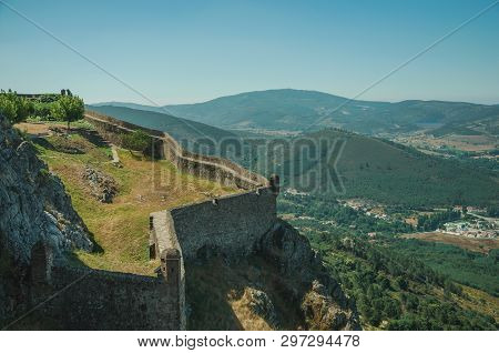 Stone Walls And Lawn Garden In Stronghold Over Crag Next To Castle, With Hilly Landscape In A Sunny
