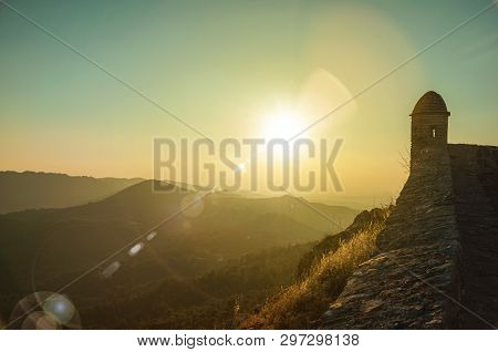 Small Watchtower And Stone Wall Over Rocky Cliff, With Hilly Landscape And Sunset Glow At Marvao. An