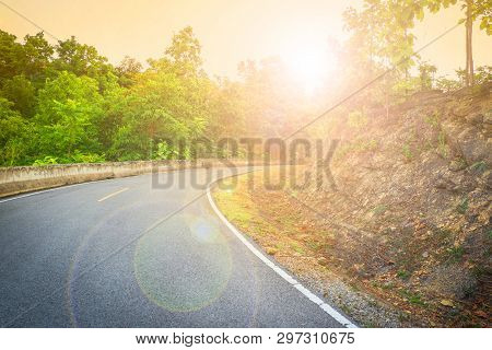 Uphill Road Curve With Sunlight In The Morning And Tree In The Roadside