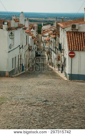 Estremoz, Portugal - July 06, 2018. Alley of old houses on slope and cobblestone causeway in a cloudy day at Estremoz. A nice little historic town with several marble buildings on eastern Portugal.
