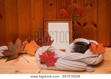 0cdbd316d25 Empty Wooden Frame, Mug Of Coffee Wrapped In Gray Woolen Scarf And Colorful Autumn  Leaves