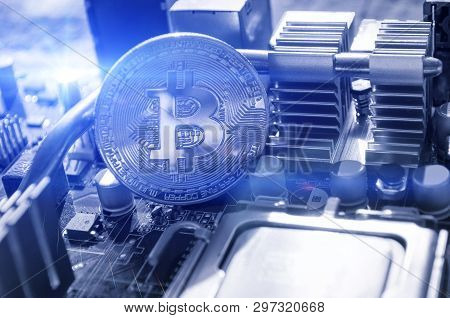 Silver bitcoin near the microprocessor. Business concept of digital bitcoin cryptocurrency. Blockchain technology, bitcoin mining concept