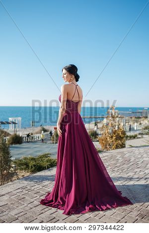 Beautiful Woman In Elegant Evening Dress. Brunette Girl With Long Healthy And Shiny  Hair. Beautiful