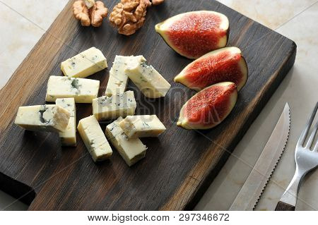 Cheese With Blue Mold  Dorblu, A Few Slices Of Figs And Walnuts Are Served On A Wooden Board. There
