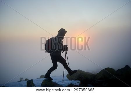 Silhouette Of Tourist Hiker Man With Backpack And Trekking Sticks Climbing On Rocky Mountain Peak On