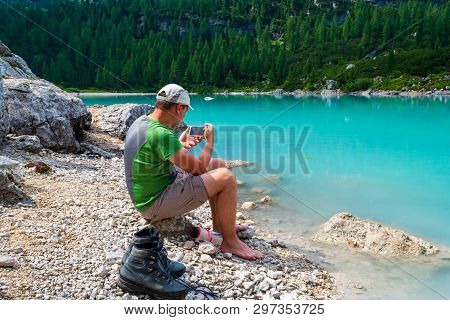 Dolomites, Italy - July 22, 2018: Barefoot Hiker Standing On A Rock With His Boots Next To Him And T