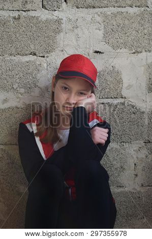Young Girl Is Sitting In Black Sports Suit, Red Cap. Concept Portrait Of A Sad Teenager.