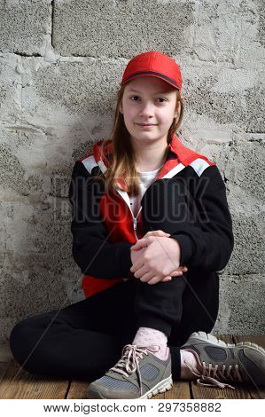 Young Girl Is Sitting In Black Sports Suit, Red Cap And Smiling. Concept Portrait Of A Pleasant Frie