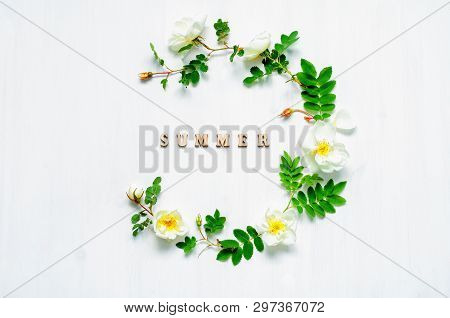 Summer flower background with composition made of white rose flowers and Summer letters on the white background. Flat lay, top view, summer composition