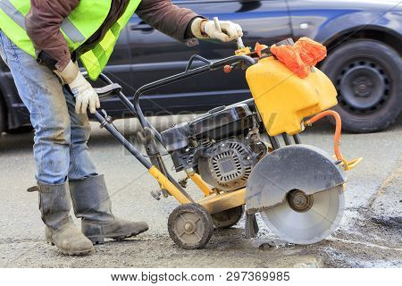 A Worker In A Green Reflective Vest Cuts A Piece Of Bad Asphalt With A Gasoline Cutter On The Carria