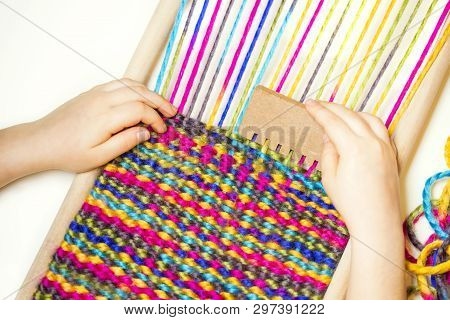 Weaving. Hands Of Little Caucasian Girl Working On Small Loom Weaving.
