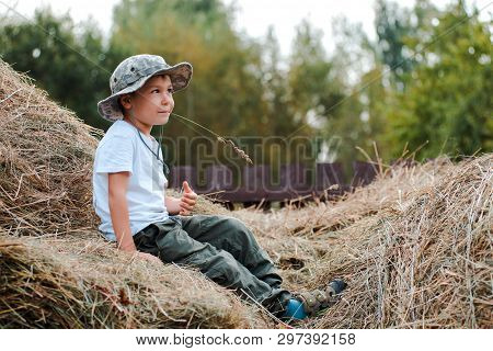 Little Boy Sitting At The Height Of A Large Haystack In The Village. The Child The Farmer. Childrens