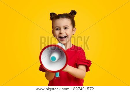 Excited Kid Leader Speaking In Megaphone And Smiling While Standing Against Yellow Background. Young