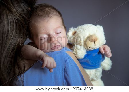 Close-up Photo Of Young Mom Holding Her Newborn Baby On Her Shoulder.