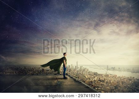 Surreal View Of Confident Superhero With Cape Stands On The Rooftop Looking Over City Horizon. Ambit