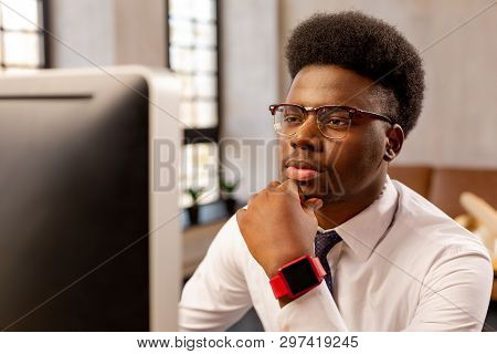 Serious Smart Young Man Touching His Chin