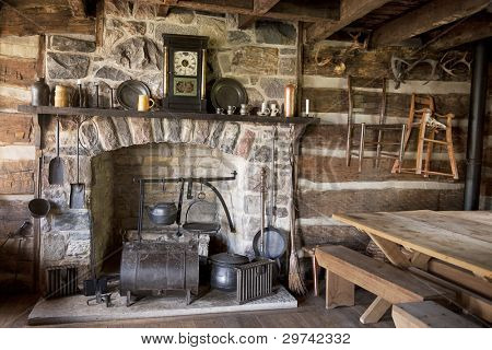 The fireplace and utensils of an old pioneer log home.