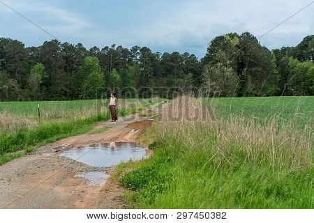 Woman in sarong standing on dirt road with her reflection in puddles poster